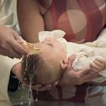 Baptême catholique avec la bénédiction par l'eau de l'enfant